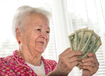 Portrait of  old woman holding money in hands  免版税图像