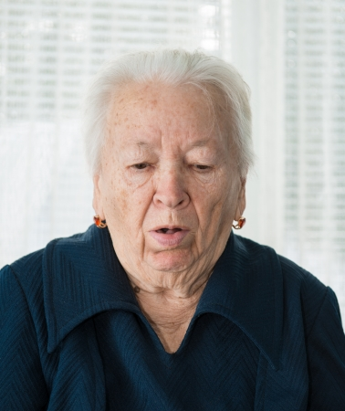 Elderly woman coughing on a white background photo