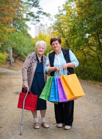 Twee volwassen vrouwen met boodschappentassen in de straat
