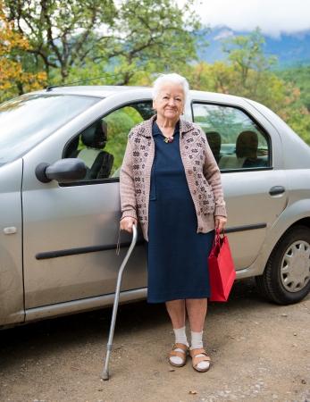 Oude vrouw stond met boodschappentassen in de buurt van de auto
