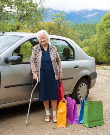 Old woman standing with shopping bags near the car