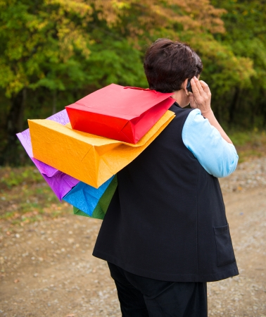 Mature woman talking on the phone and holding shopping bags photo