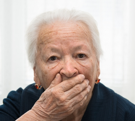 Old woman yawning with hand in front of her mouth