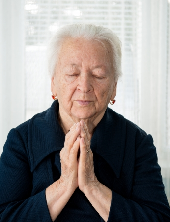 Portrait of praying old woman photo