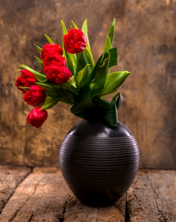 Beautiful red tulips in black vase on a wooden background photo