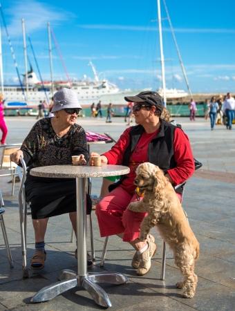 Two women drinking coffee near the harbor photo