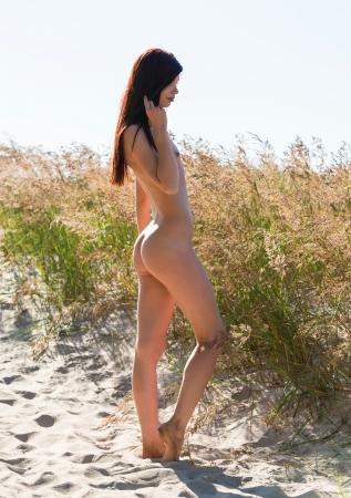 naked woman: Портрет молодой обнаженной женщины на песчаном пляже