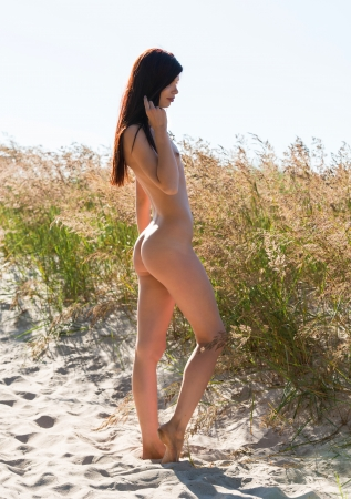 Portrait of a young naked woman on a sandy beach