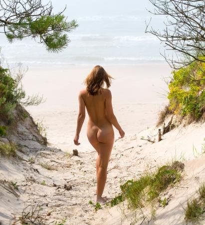 naaktstrand: Jonge vrouw naakt lopen op een zandstrand