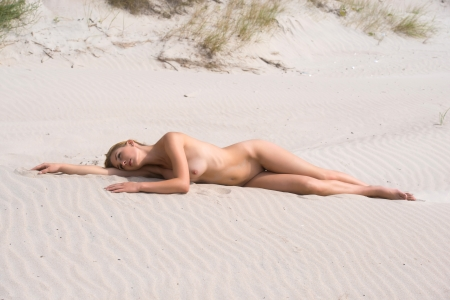 erotic breast: Beautiful young naked woman sunbathing on the beach