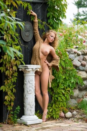 nudo integrale: Bella donna nuda in posa vicino alla vecchia casa di campagna
