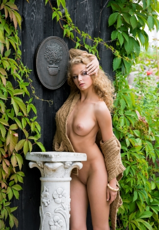 nude: Beautiful nude woman posing near the old country house