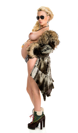Blond pregnant woman in fur coat on a white background 免版税图像