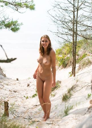 woman nude: Joven mujer desnuda de pie en una playa de arena