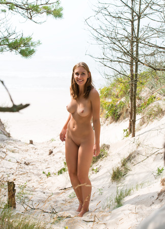 Young nude woman standing  on a sandy beach Stock Photo