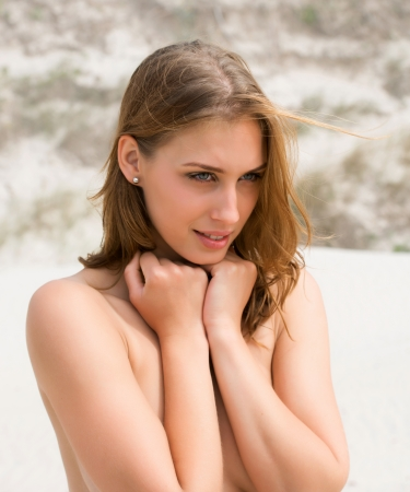 Portrait of a topless young woman covering her breasts by hands photo