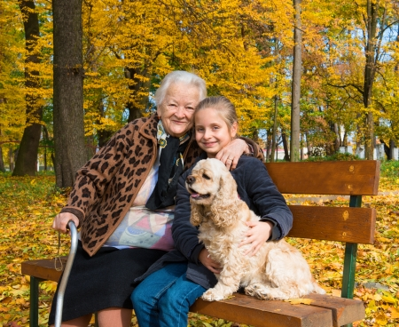 autumn dog: Grandmother and child sitting on the bench in the autumn park  Stock Photo