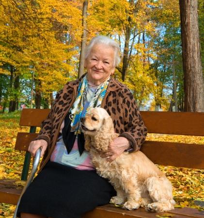 Oude vrouw zit op een bankje met een hond in de herfst park