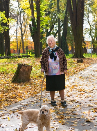 Old woman walking  in the autumn park