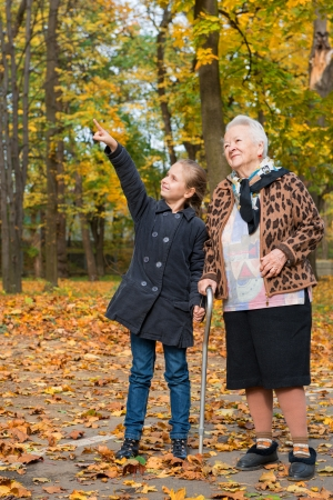 Grandmother and child walking  in the autumn park  photo