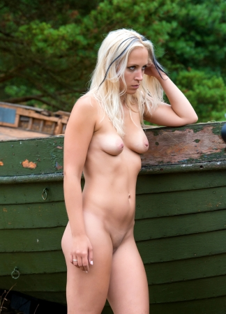 nudity girl: Young nude woman posing near a boat against the nature background