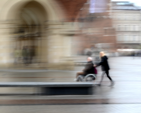 Woman pushing man in a wheelchair in motion blur
