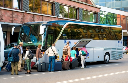 Bus for tourists transportation and group of tourists neat hotel Standard-Bild