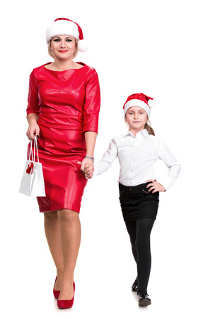 Mother and daughter in santa hats on a white  photo