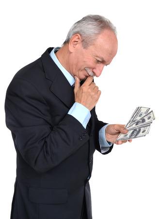 fortunate: Elderly man holding dollars