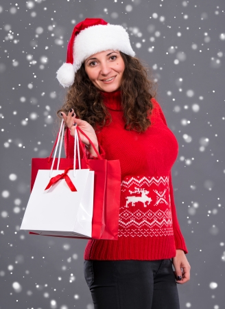Smiling woman in santa hat with shopping bags, christmas, x-mas, winter, snow falls photo