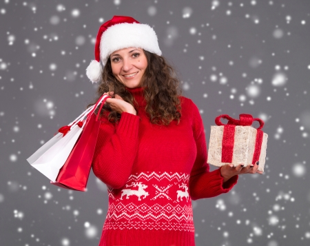 Smiling woman in santa hat with shopping bags and gift box, christmas, x-mas, winter, snow falls photo