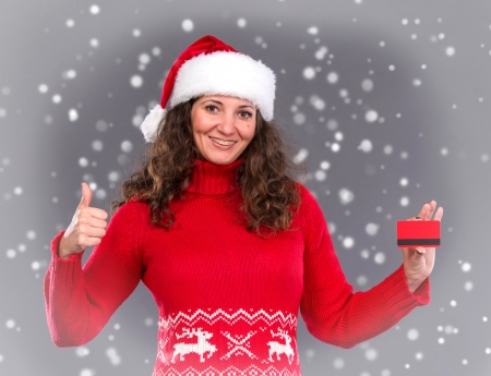 Smiling woman in santa hat credit card, christmas, x-mas, winter, snow falls photo