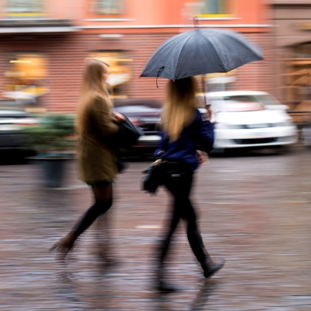 People walking in the street on a rainy day in motion blur photo