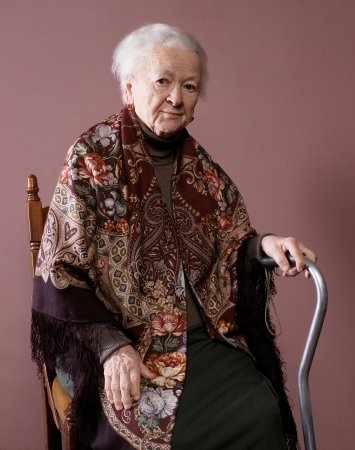 Old woman sitting on a chair with a cane on brown background