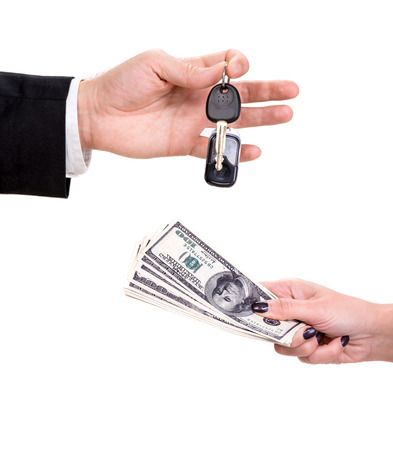 Male hand holding a car key and handing it over to another person Woman holding dollars  photo