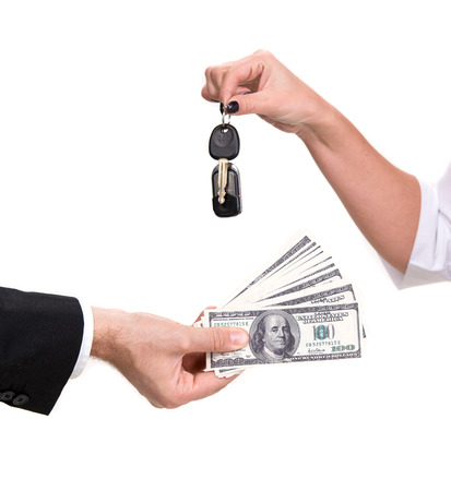 Female hand holding a car key and handing it over to another person Man holding dollars  photo