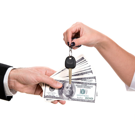 cash in hand: Female hand holding a car key and handing it over to another person Man holding dollars