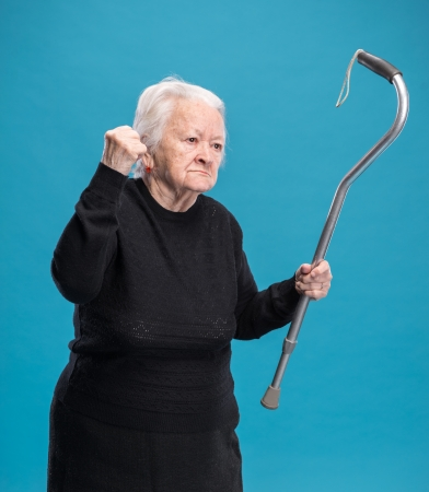 Old angry woman threatening with a cane on a blue background photo