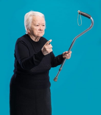 Old angry woman threatening with a cane on a blue background
