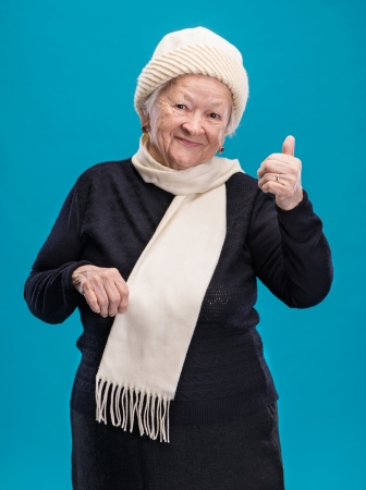 Old woman showing ok sign on a blue background photo