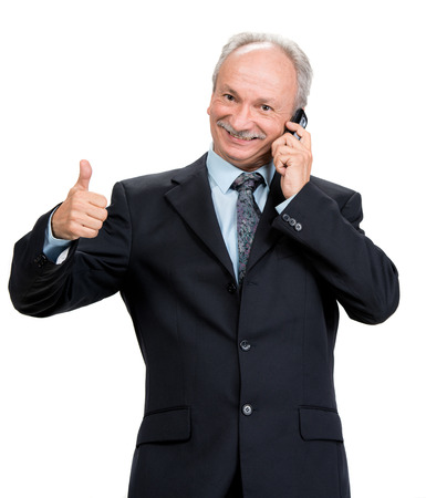 Senior businessman with cell phone on a white background photo