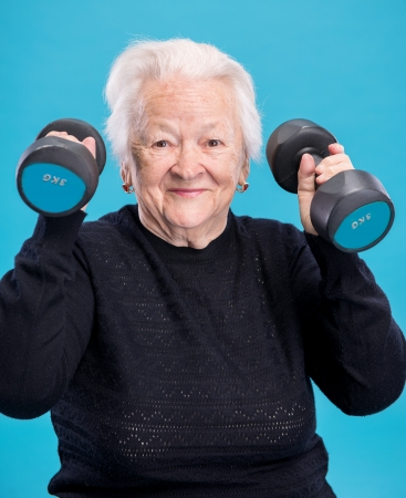 Happy old woman making fitness training with dumbbells on a blue background Фото со стока