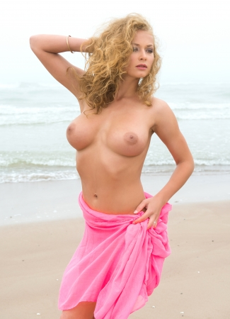 nude outdoors: Young nude woman in pink fabric posing on sea beach in foggy day