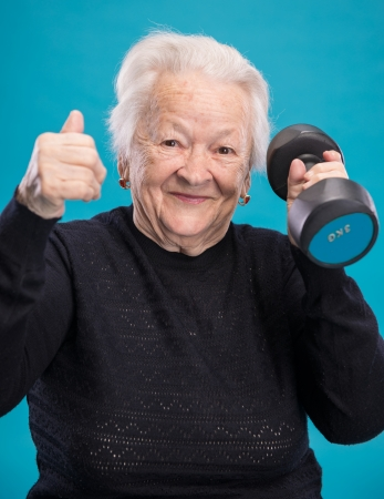 Happy old woman making fitness training with dumbbells on a blue background 免版税图像