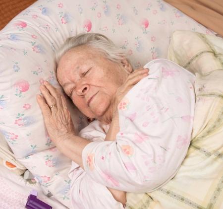 Sick senior woman lying at bed 免版税图像