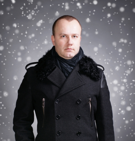 Portrait of young handsome man wearing winter coat and scarf  photo