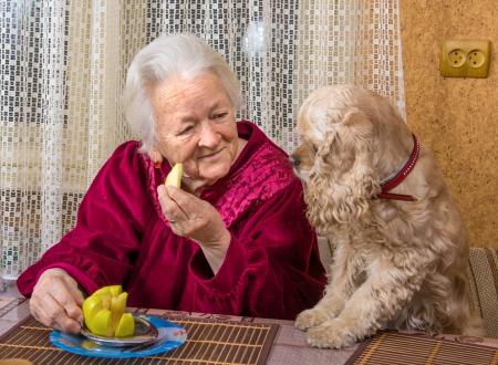 Oude vrouw en haar hond in de keuken