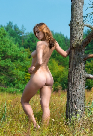nude pose: Beautiful young naked woman  posing near an old tree