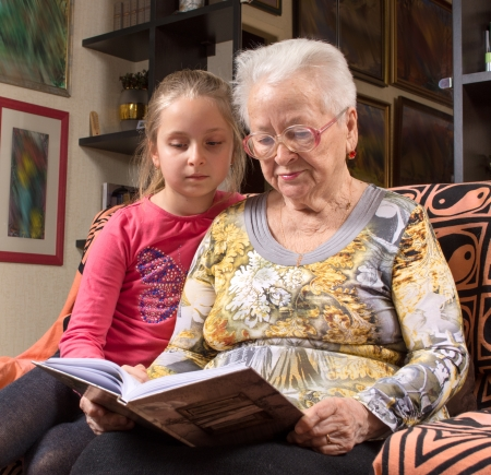 Grandmother and granddaughter reading a book photo