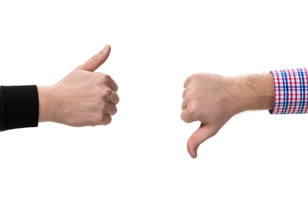 Two gesturing hands, with thumbs up and down photo